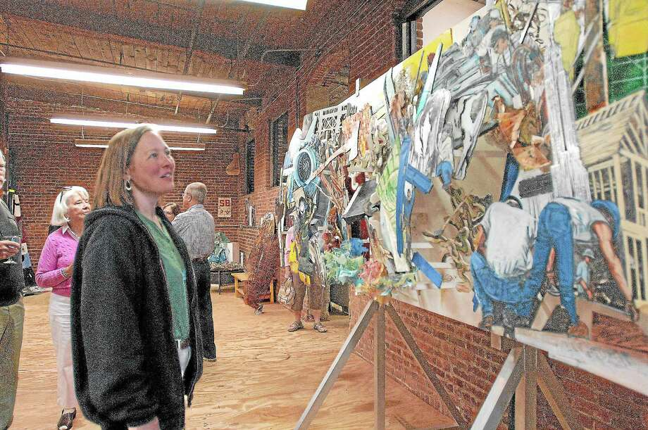 Deb Majewski admires a piece of artwork at the American Mural Project on Whiting Street in Winsted. Photo: Register Citizen File Photo