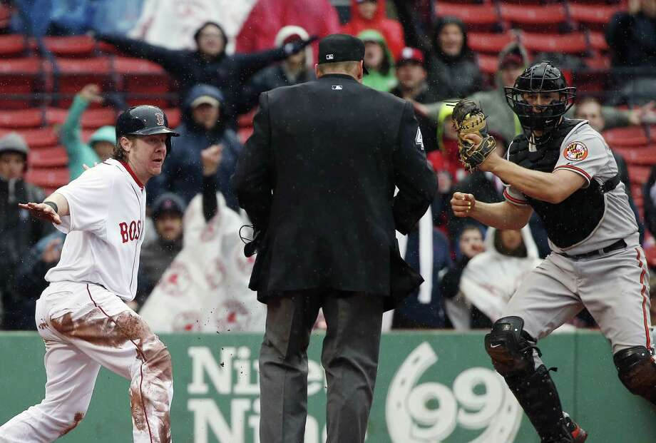 Ryan Hanigan, left, and the Orioles' Ryan Lavarnway look for the call after Hanigan scored on a double by Dustin Pedroia in the sixth inning Monday. Photo: Michael Dwyer — The Associated Press  / AP