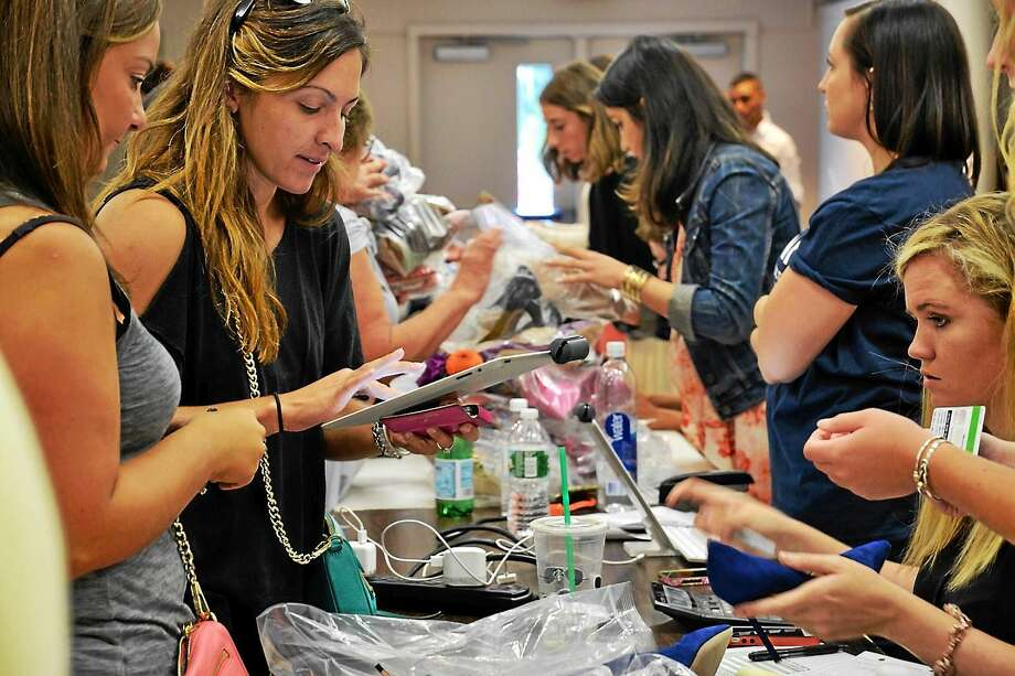 A sample sale of high-end shoes in Bantam on Aug. 15 raised nearly $200,000 for scholarships for UConn animal science students. Photo: Photo By Susan Taff
