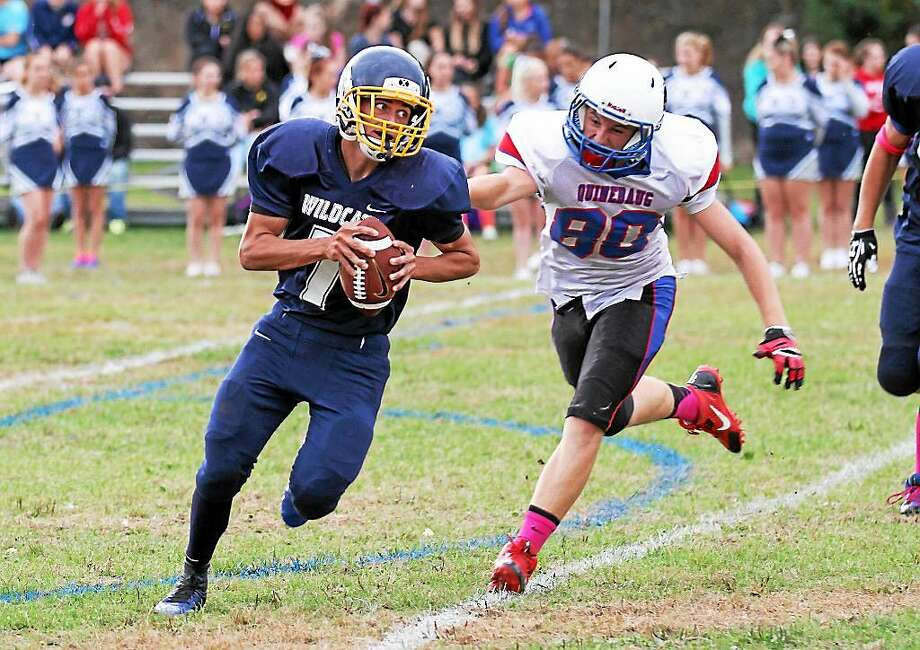Marianne Killackey — Register Citizen Graduated Wolcott Tech quarterback Mickey Ross runs for yardage as a Quinebaug defender gives chase during a game last season. Wolcott Tech is taking a break from varsity play in 2015 due to low numbers. Photo: Journal Register Co.