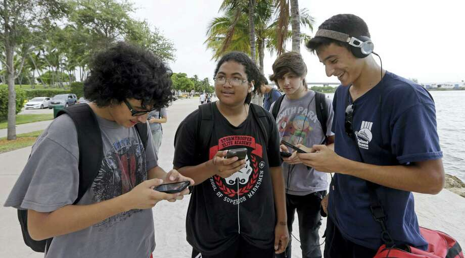 """Pokemon Go players Brian Vega, left,  Peyton Ruiz, second from left, and Max Marrero, right, check their smartphones as they try to find Pokemon, Tuesday, July 12, 2016, at Bayfront Park in downtown Miami. The """"Pokemon Go"""" craze has sent legions of players hiking around cities and battling with """"pocket monsters"""" on their smartphones. It marks a turning point for augmented reality, or technology that superimposes a digital facade on the real world. Photo: AP Photo/Alan Diaz   / AP"""