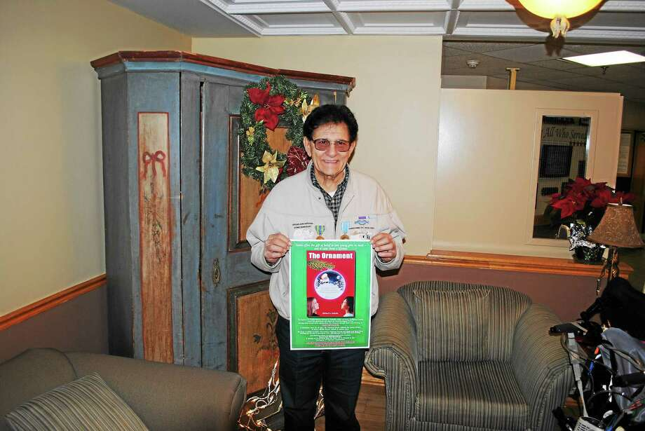 "Mike Galitello, with a poster advertising his latest book for children, ""The Ornament."" Photo: BEN LAMBERT — The Register Citizen"