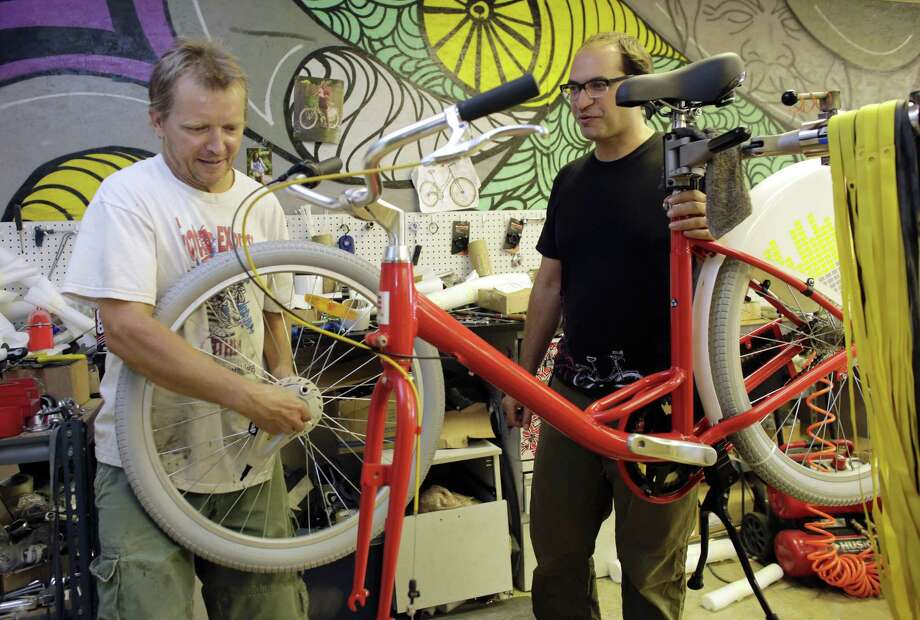 Avery Pack, president of Republic Bike, right, talks with employee Tim Hignett, left, as he assembles a fleet bicycle manufactured at Republic Bike, in Dania Beach, Fla. Photo: Lynne Sladky — The Associated Press  / AP