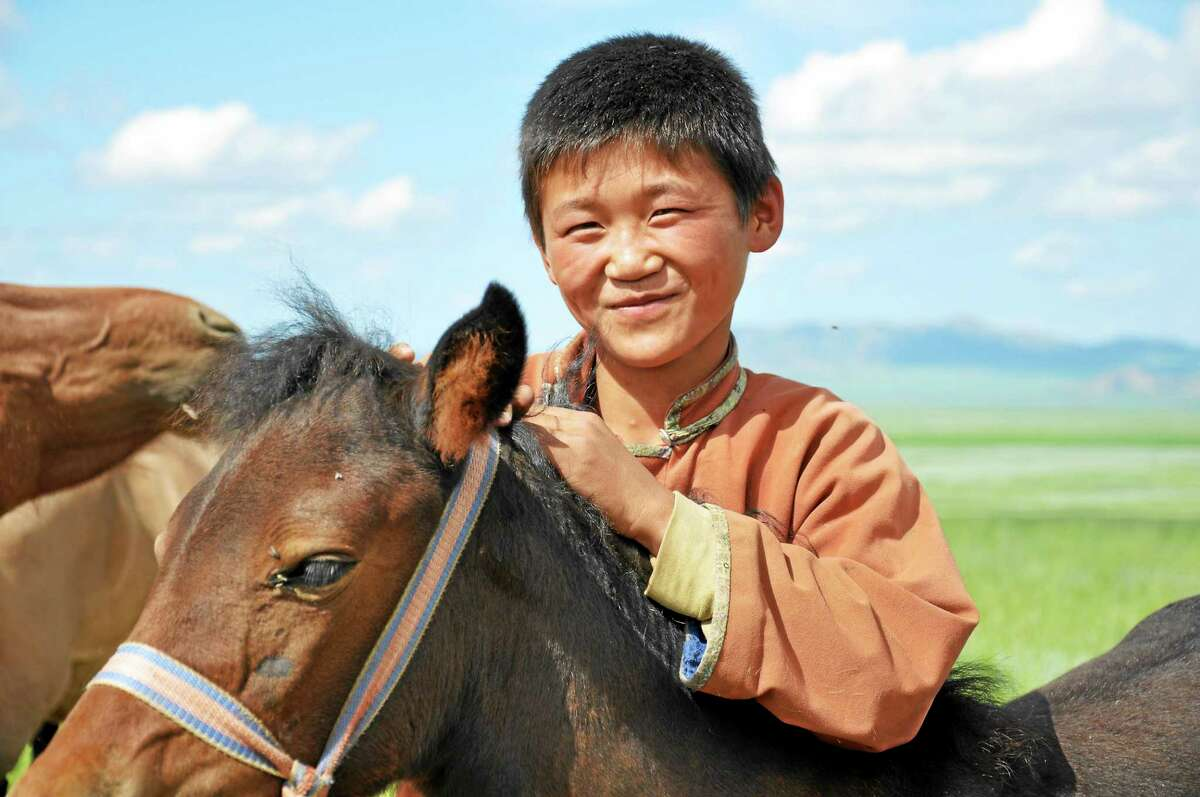 A Mongolian boy with his horses.