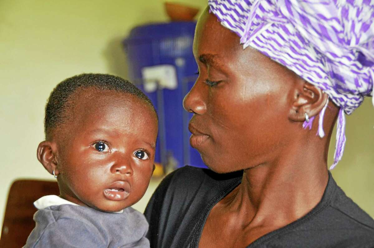 A mother and baby in the doctor's office. Both are suffering with malaria which is rampant in Burkina Faso.