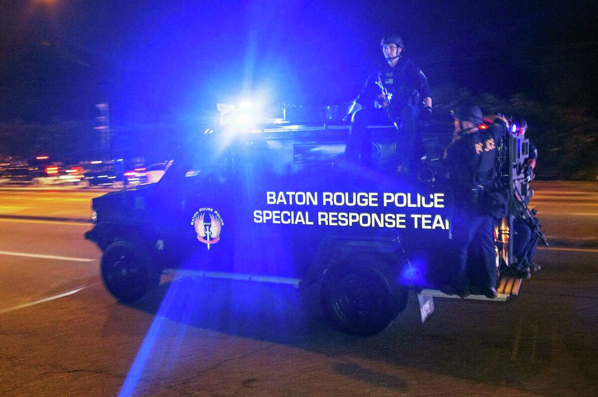Sheriff Deputies ride outside an armored vehicle on Airline Highway, a major road that passes in front of the Baton Rouge Police Department headquarters, as they attempt to clear protesters from the road in Baton Rouge, La.