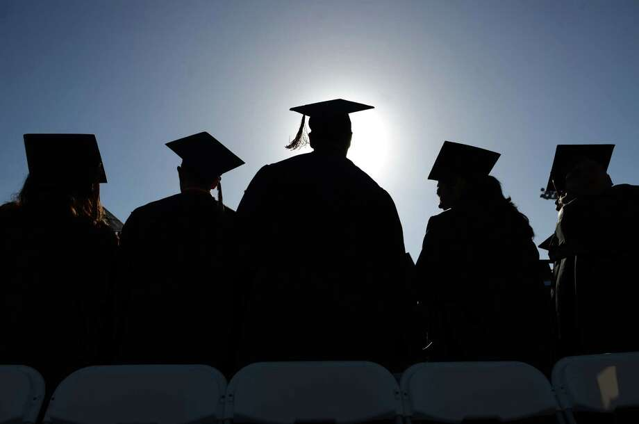 In this June 18, 2014 photo, High School graduates stand and sing during graduation ceremonies in Santa Ana Bowl. The nation's high school graduation rate has ticked up slightly to 82 percent, a new high. Photo: AP Photo/The Orange County Register, Mark Felix, File  / ORANGE COUNTY REGISTER