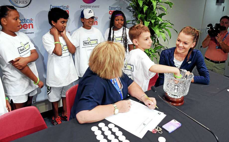 WTA Supervisor Donna Kelso, center, gets assistance with the draw ceremony from Ethan Ofek, 9, of New Haven and other members of New HYTEs junior team tennis program at the Connecticut Open on Friday. Agnieszka Radwanska, far right, also helped with the draw. Photo: Arnold Gold — Register