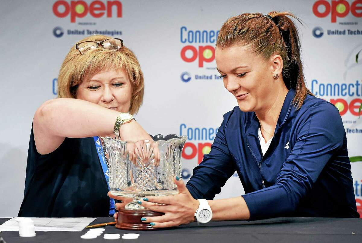 WTA Supervisor Donna Kelso, left, gets assistance with the draw from Agnieszka Radwanska Friday at the Connecticut Open.
