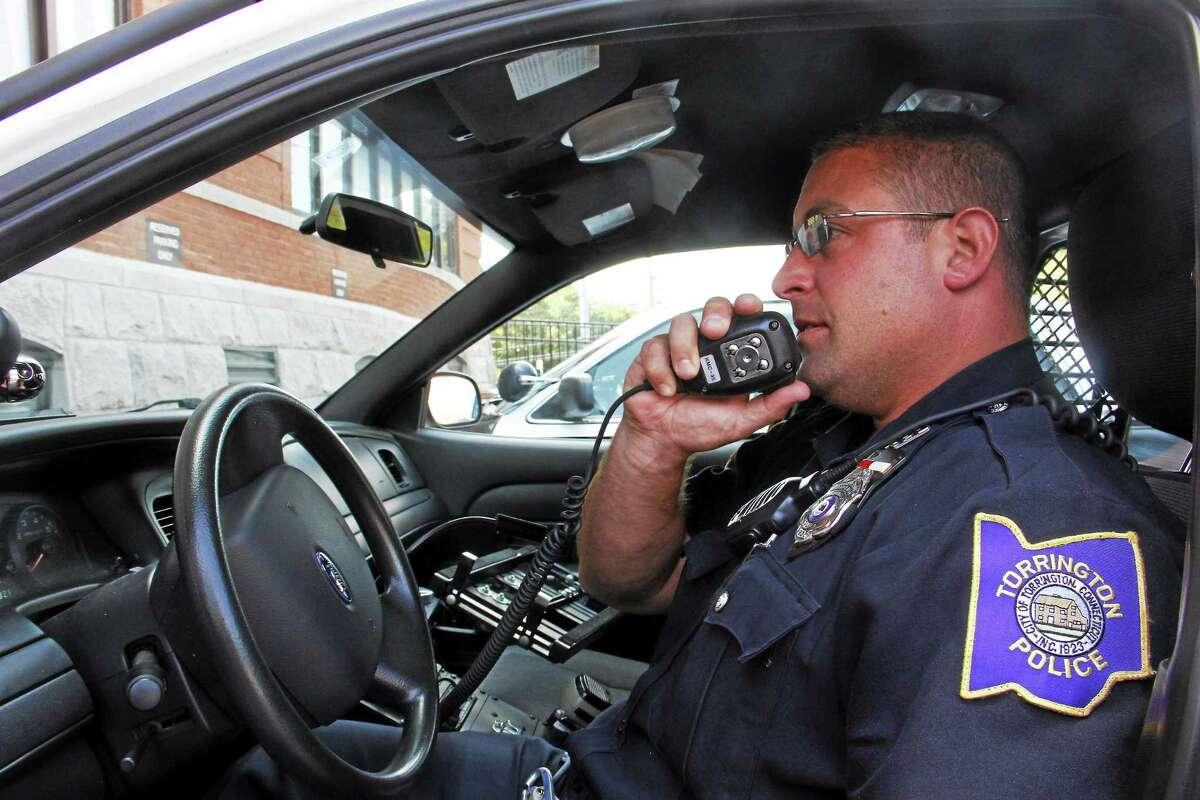 Torrington Police Department Patrolman William Bernabucci simulates radio communication in this 2014 file photo outside the department's headquarters.