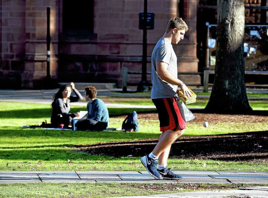 Yale freshman Quintin Herbert walks through Yale University's Old Campus in New Haven during finals week Tuesday. Herbert is from Cincinnati, Ohio, where the weather has been just as warm. Photo: Arnold Gold — New Haven Register