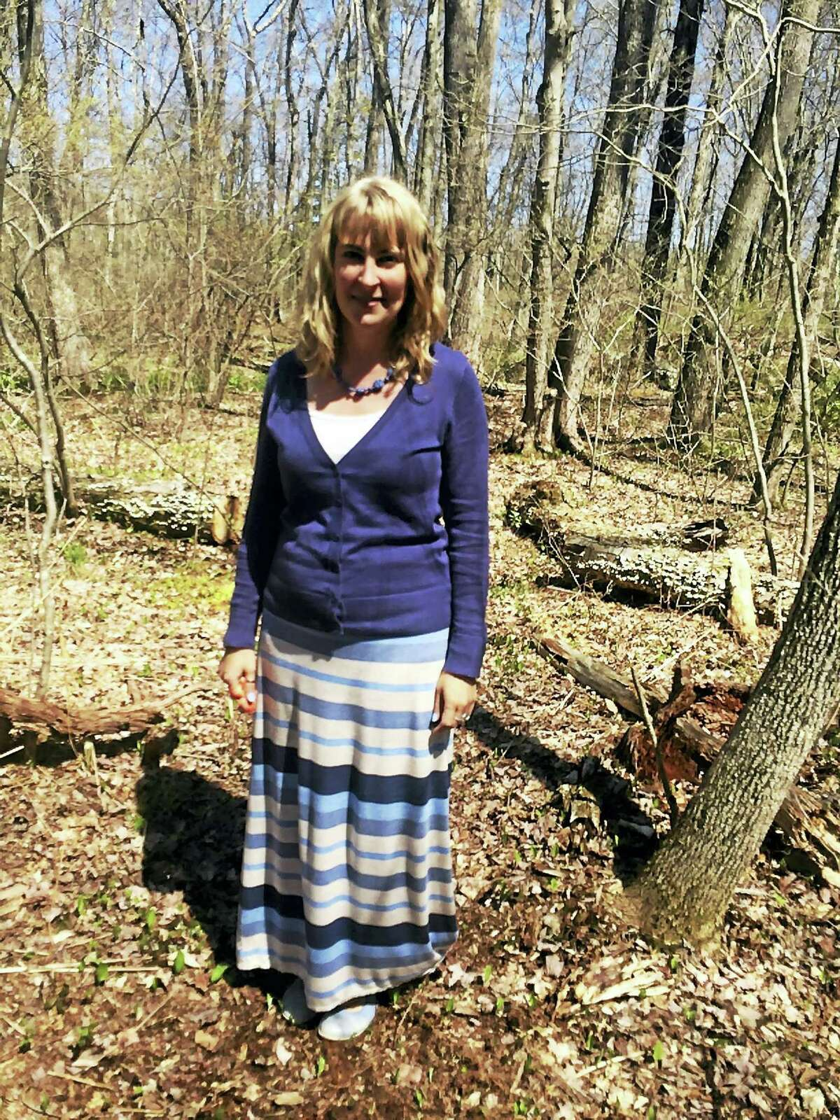 Cara Johnson, head of the Litchfield Montessori School, shows a spot in the woods where benches will be added for an outdoor classroom.