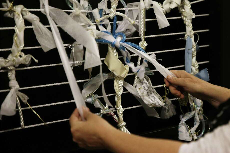 FILE- In this May 22, 2015 file photo, artist Meg Saligman shows knots tied to a mock-up of an art installation at her studio in Philadelphia. The installation is planned to be in the shape of a latticed grotto and will greet Pope Francis and millions of others when they travel to Philadelphia this fall. Visitors will be invited to leave their own problems behind in the form of knots affixed to its walls, or help others by loosening and removing a knot already in place. (AP Photo/Matt Slocum, File) Photo: AP / AP