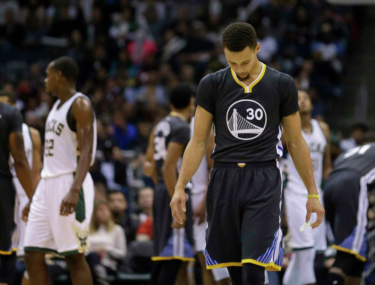 The Warriors' Stephen Curry looks down during the second half Saturday's loss to the Bucks.