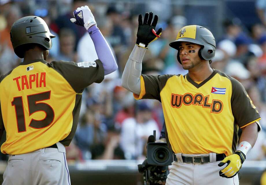 Yoan Moncada, right, greets teammate Raimel Tapia after hitting a two-run home run in the All-Star Futures game on Sunday in San Diego. Photo: Lenny Ignelzi — The Associated Press  / Copyright 2016 The Associated Press. All rights reserved. This material may not be published, broadcast, rewritten or redistribu
