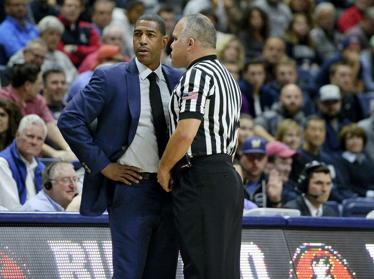 Official Jose Carrion, right, has a word with Connecticut head coach Kevin Ollie in the first half of an NCAA college basketball game, Friday, Nov. 11, 2016, in Storrs, Conn. (AP Photo/Jessica Hill)