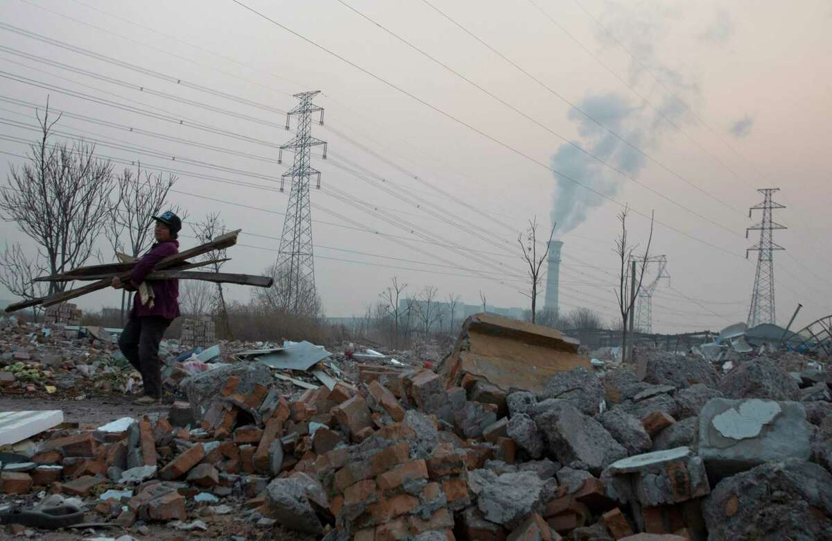 In this photo taken Dec. 12, 2015, a scrap collector salvages material from a demolished neighborhood near a chimney spewing smoke, in Beijing, China. China's push for a global climate pact was partly because of its own increasingly pressing need to solve serious environmental problems, observers said Sunday.