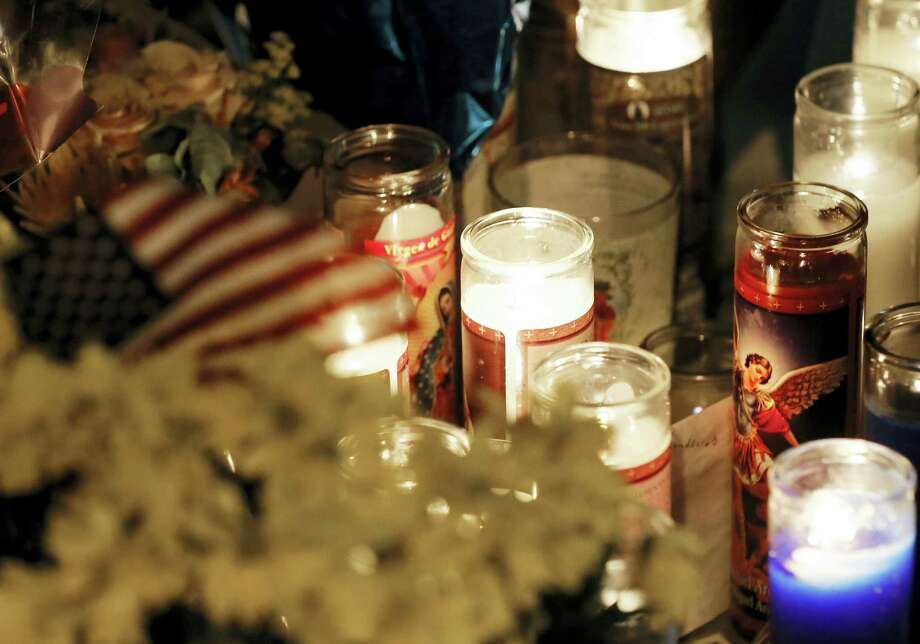 An American flag sits atop flowers by candles at a makeshift memorial in honor of the slain Dallas police officers in front of police headquarters in Dallas on  Saturday. Photo: ASSOCIATED PRESS  / Ap