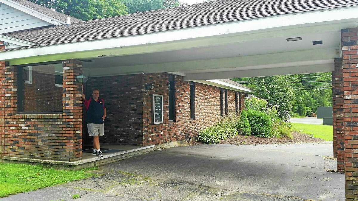Pastor Allen Latimore stands outside of Advent Christian Church in Torrington. He hopes to utilize a carport as a drive-thru prayer service.