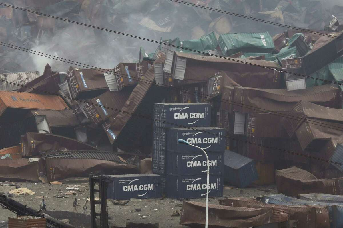In this photo taken Friday, Aug. 14, 2015, Chinese men walk through the site of an explosion at a warehouse in northeastern China's Tianjin municipality. The man unveiled as principal owner of the warehouses at the center of deadly blasts in Tianjin also is on the board of a state-owned company that is ultimately controlled by the same powerful entity investigating the explosions, an Associated Press review of public documents found.