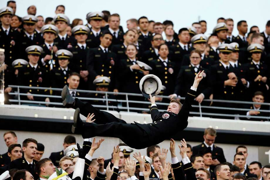 A Navy Midshipman is tossed in the air as Navy fans celebrate a touchdown during Saturday's game in Philadelphia. Photo: Matt Slocum — The Associated Press  / AP