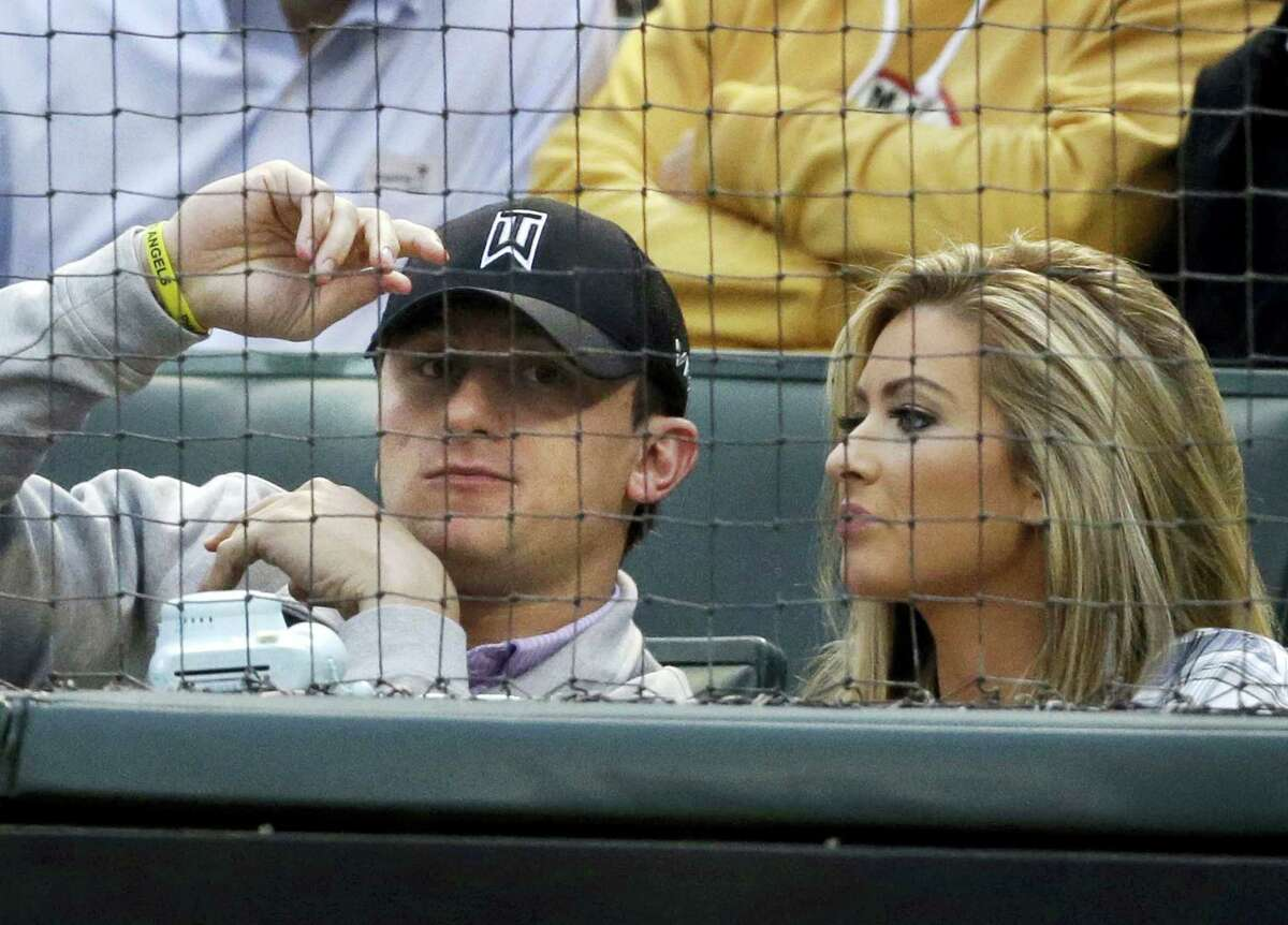 In this 2015 file photo, Browns quarterback Johnny Manziel, left, sits with Colleen Crowley during a baseball game in Arlington, Texas.