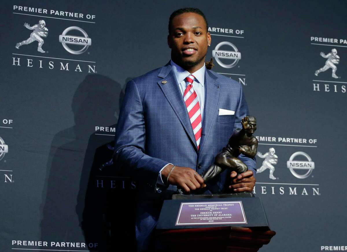 Alabama's Derrick Henry poses for photos after winning the Heisman Trophy on Saturday.