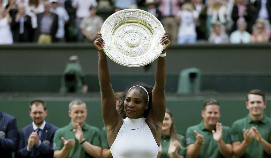 Serena Williams holds up her trophy after winning the women's singles final at Wimbledon on Saturday. Photo: Tim Ireland — The Associated Press  / Copyright 2016 The Associated Press. All rights reserved. This material may not be published, broadcast, rewritten or redistribu