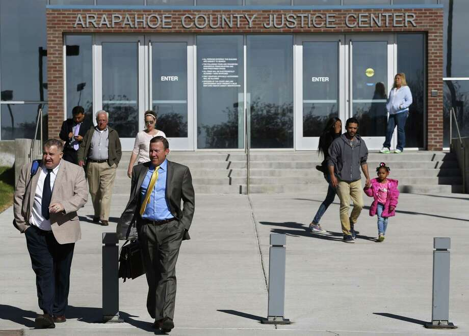People enter and leave the Arapahoe County District Court in Centennial, Colo., Monday April 13, 2015. The jury selection process in the trial of Aurora theater shooting suspect James Holmes entered its final stage Monday when attorneys began questioning prospective jurors as a large group. Holmes is charged with killing 12 people and wounding more than 50 in a crowded Aurora, Colorado movie theater in 2013. (AP Photo/Brennan Linsley) Photo: AP / AP