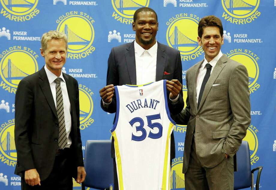 Kevin Durant, center, joins Golden State Warriors head coach Steve Kerr, left, and general manager Bob Myers during a news conference on Thursday in Oakland, Calif. Photo: Beck Diefenbach — The Associated Press  / FR170639 AP