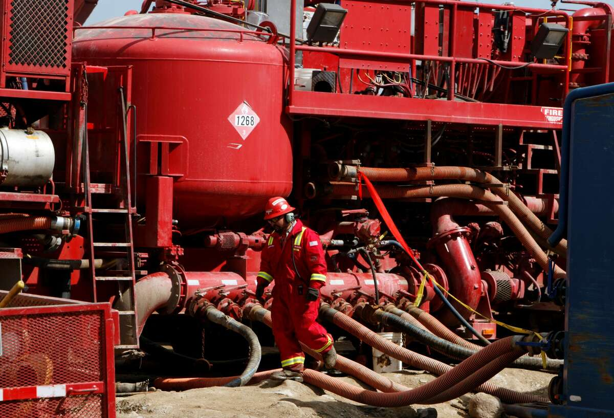 In this 2009, an unidentified worker steps through the maze of hoses being used at a remote fracking site being run by Halliburton for natural-gas producer Williams in Rulison, Colo.