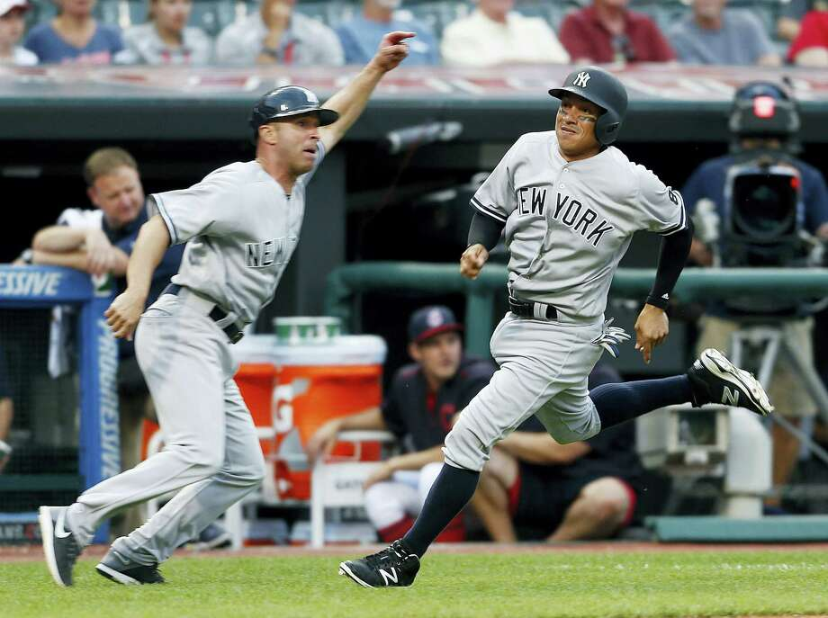 Ronald Torreyes (17) gets waved home by third base coach Joe Espada to score the go-ahead run against the Indians on Saturday. Photo: Ron Schwane — The Associated Press  / AP 2016