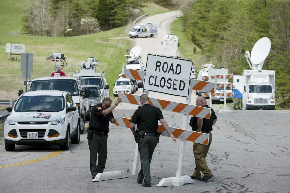 In this Friday, April 22, 2016, file photo, authorities set up road blocks at the intersection of Union Hill Road and Route 32 at the perimeter of a crime scene, in Pike County, Ohio. As the investigation into the killings of eight family members in rural Ohio enters its fifth day, more details are being released. Pike County Prosecutor Rob Junk told The Columbus Dispatch Monday, April 25, 2016, that the marijuana operations discovered at three of the four crime scenes included a grow-house sheltering hundreds of plants.