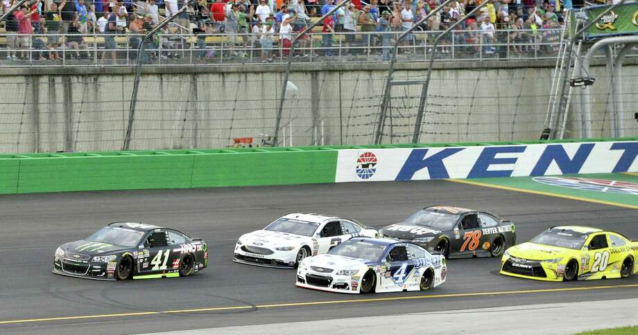 Drivers jockey for spots during a restart at Kentucky Speedway on Saturday. Photo: Timothy D. Easley — The Associated Press  / FR43398 AP