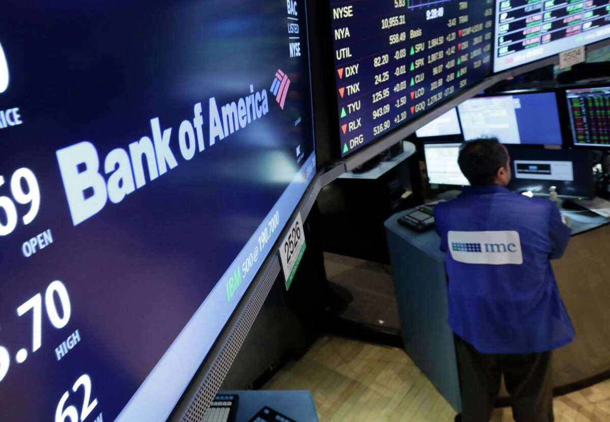 FILE - In this Aug. 21, 2014 file photo, an IMC specialist works at his post where Bank of America is traded on the floor of the New York Stock Exchange. Wild swings in the stock, bond and currency markets in the first three months of 2015 are likely to translate into bigger profits for big U.S. banks, analysts say.