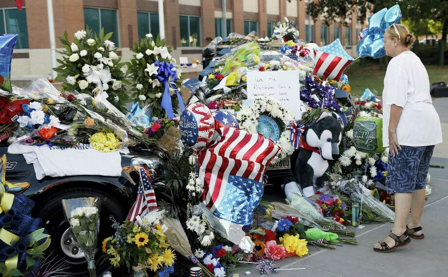 Mary Savage visits a make-shift memorial in front of the Dallas police department, Saturday, July 9, 2016, in Dallas. Five police officers are dead and several injured following a shooting in downtown Dallas Thursday night. Photo: AP Photo/Eric Gay   / Copyright 2016 The Associated Press. All rights reserved. This material may not be published, broadcast, rewritten or redistribu