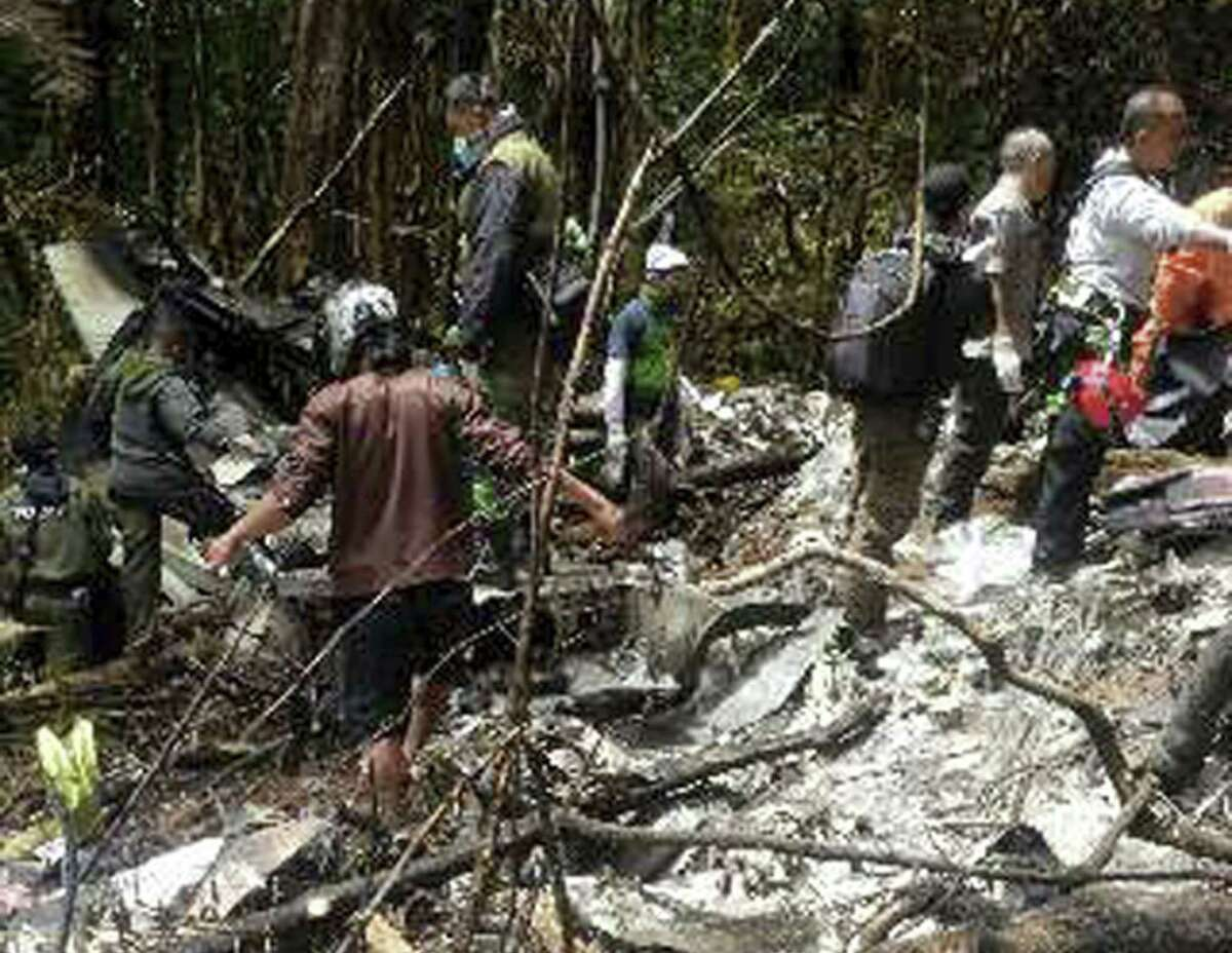 Officials and rescue workers gather by plane wreckage strewn across dense terrain in a remote area of Pegunungan Bintang, Papua province, Indonesia, Tuesday, Aug. 18, 2015. The Trigana Air Service plane that went missing two days ago was destroyed when it slammed into a mountain, killing all 54 people on board, the country's top rescue official said.