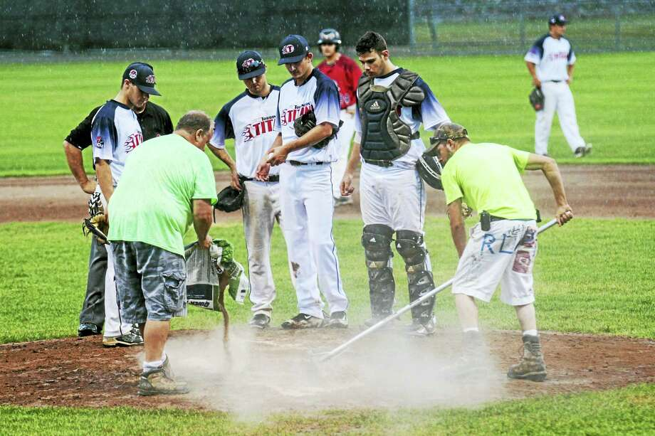 Photo by Marianne KillackeyThe Torrington Titans look on as Fuessenich Park groundskeepers try to salvage the pitchers mound in Friday night's rainout. Photo: Journal Register Co. / 2015