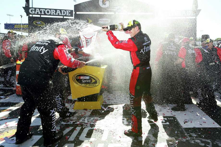 Carl Edwards sprays his crew with champagne after winning at Richmond International Raceway on Sunday. Photo: Chet Strange — The Associated Press  / FR171360 AP