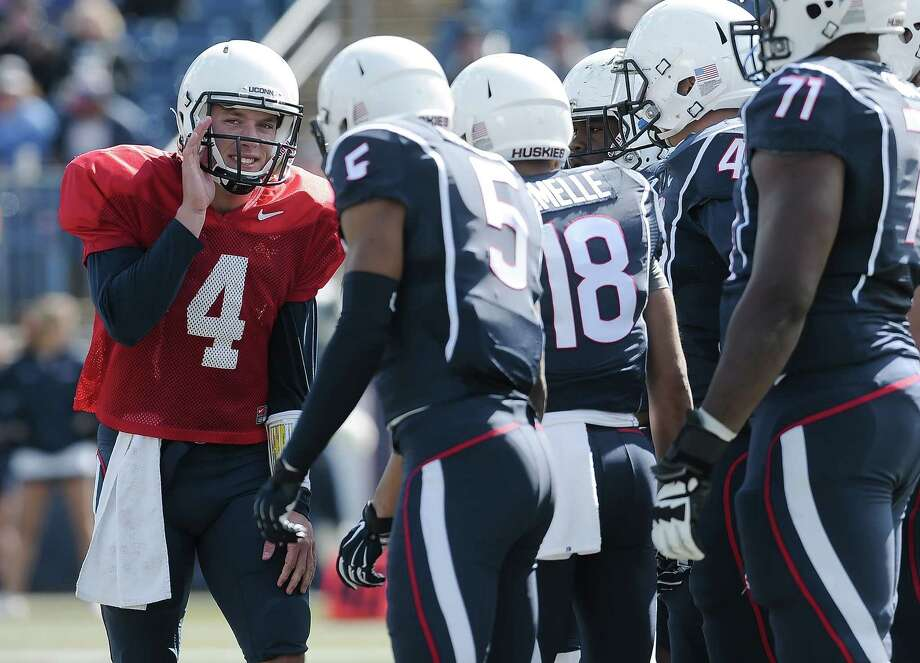 UConn sophomore quarterback Bryant Shirreffs, left, talks with his team during the first half of the Blue-White spring game at Rentschler Field on Saturday. Photo: Jessica Hill — The Associated Press  / FR125654 AP