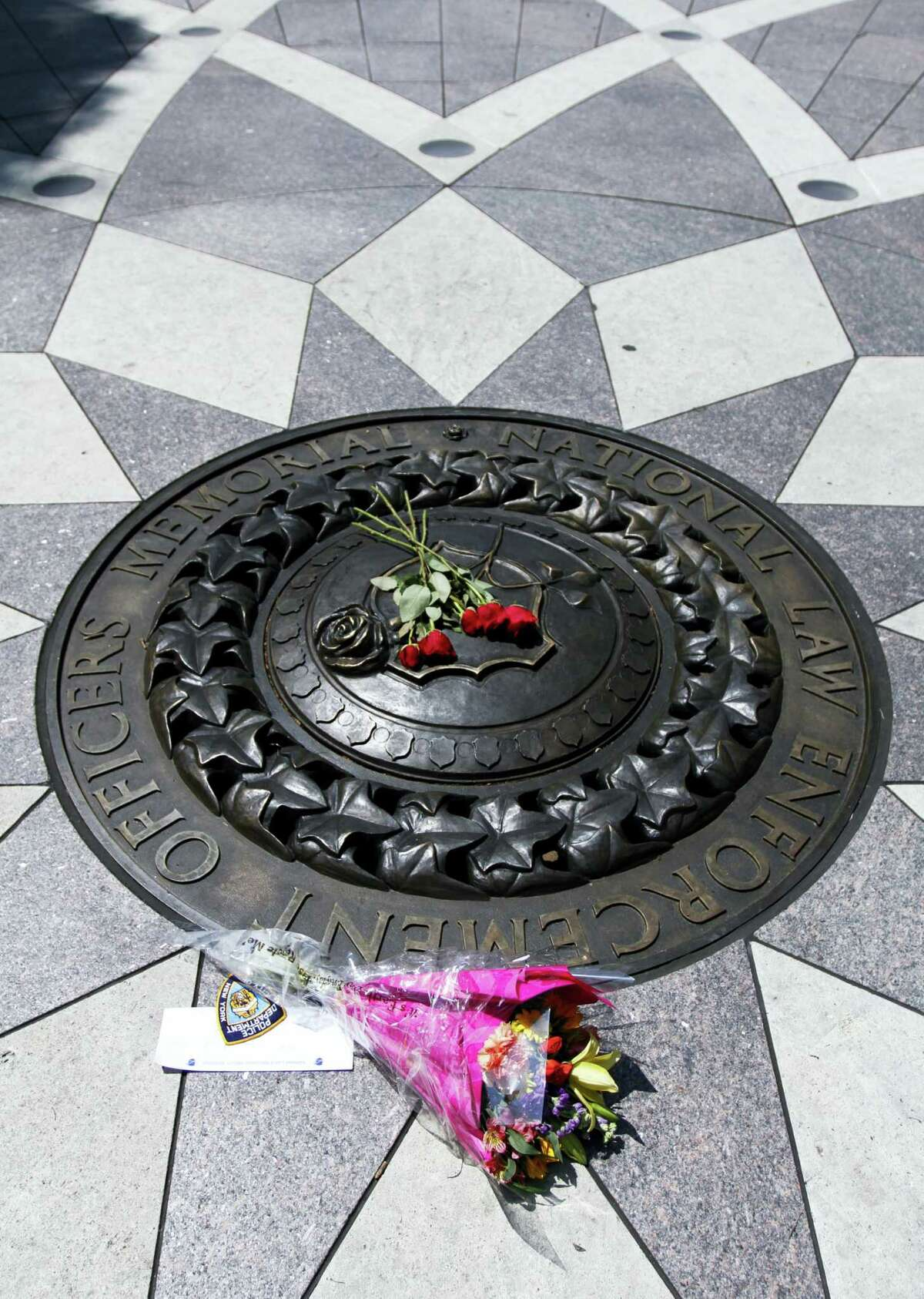 Five red roses and a bouquet of flowers with a note of support for the Dallas Police Department lies on the bronze medallion at the National Law Enforcement Officers Memorial in Washington, Friday, July 8, 2016. Five officers were killed in Dallas on Thursday.