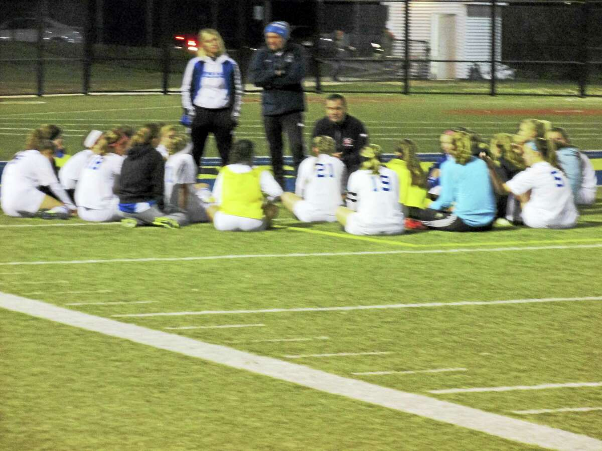 Lewis Mills coach Dave Francalangia (kneeling) talks strategy for an even second half in a Class M girls soccer semifinal loss to Immaculate Monday night at Waterbury's Municipal Stadium.