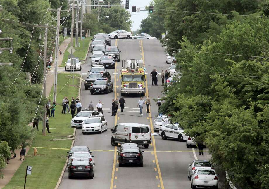 Police investigate a scene in Ballwin, Mo., Friday, July 8, 2016, after a Ballwin police officer was shot during a confrontation with a man on a street. Authorities say the wounded police officer is hospitalized didn't offer any immediate word about the officer's medical status. A suspect is in custody, and a handgun has been recovered. Photo: Cristina Fletes — St. Louis Post-Dispatch Via AP / St. Louis Post-Dispatch