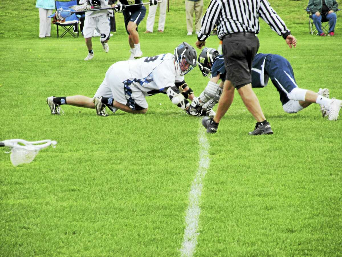 Photo by Peter WallaceThe Spartans and Indians face off in a boys lacrosse game at Lewis Mills High School Saturday afternoon.