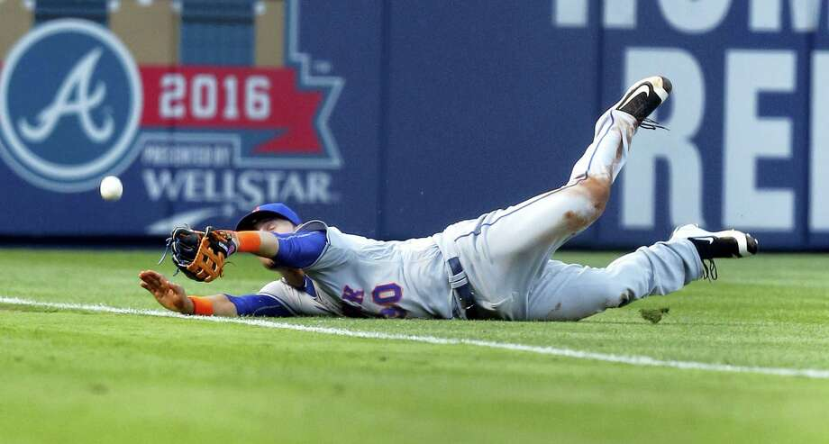 Mets left fielder Michael Conforto dives for a pop fly during the first inning on Saturday. Photo: Butch Dill — The Associated Press  / FR111446 AP