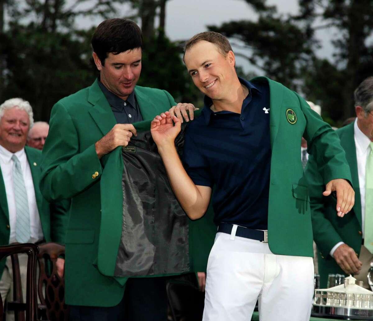 Bubba Watson helps Jordan Spieth put on his green jacket after Spieth won the Masters Sunday in Augusta, Ga.