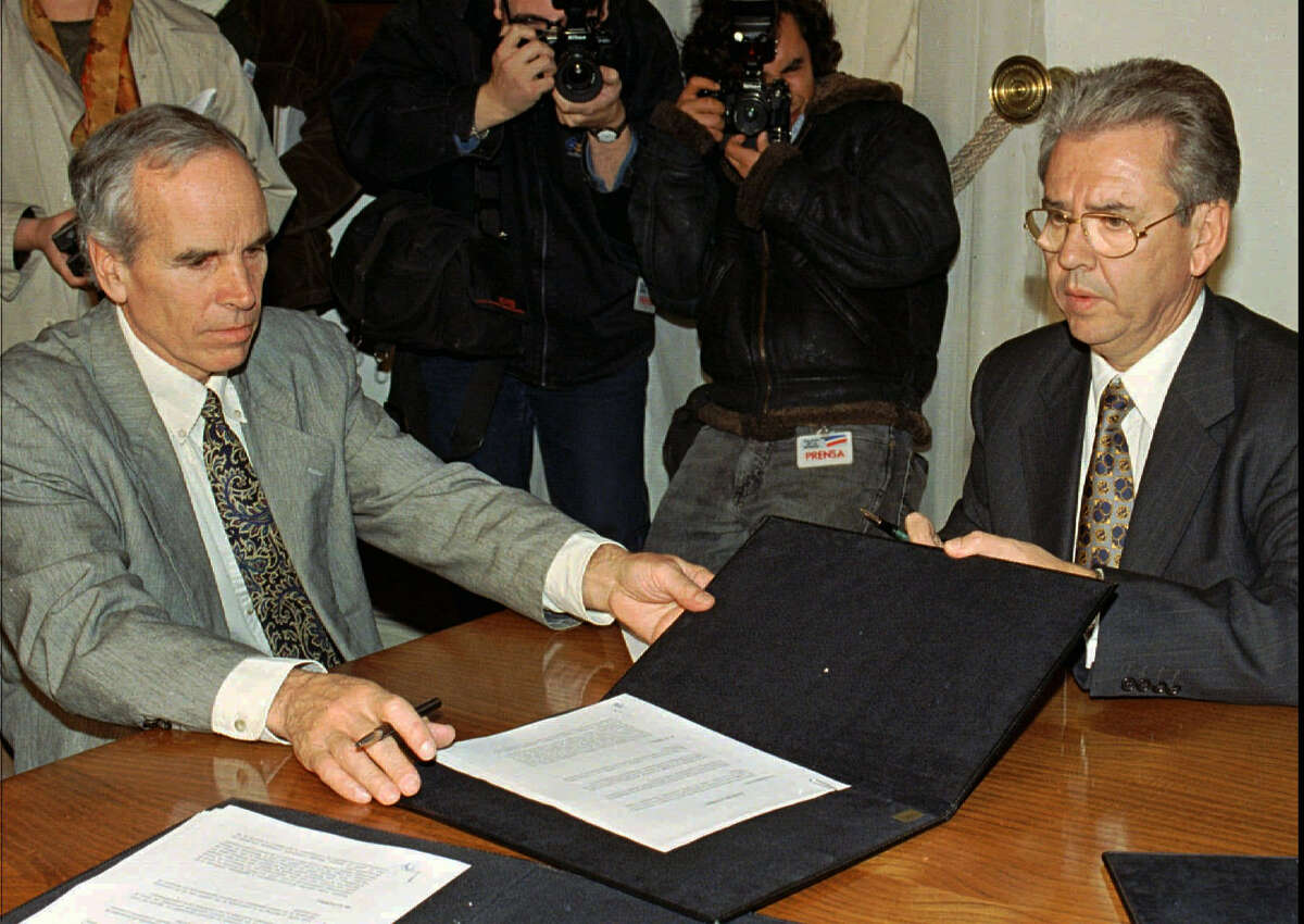 In this July 7, 1997, file photo, American millionaire Douglas Tompkins, left, and Juan Villarzu, chief of staff of the Chilean president, hold the text of an accord signed in Santiago, Chile. Officials in Chile said Tuesday, Dec. 8, 2015, that the wealthy U.S. businessman and environmental activist has died from severe hypothermia in a kayaking accident.