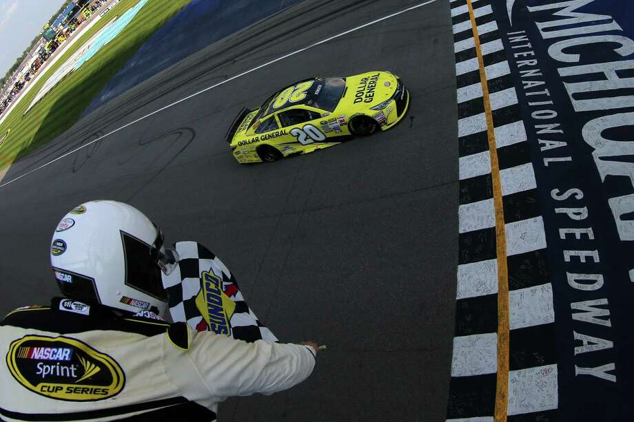 In this photo taken with a fisheye lens provided by NASCAR, Matt Kenseth takes the checkered flag to win the Pure Michigan 400 Sunday in Brooklyn, Mich. Photo: The Associated Press  / NASCAR