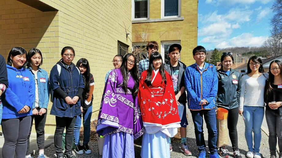 "Sally Ming, 17, and Naomi Nin, 18, stand in the foreground wearing traditional Chinese outfits with other exchange students from Winsted's Gilbert School. The group performed folk dances at The Beardsley & Memorial Library on Saturday morning as part of the ""One World, Many Stories!"" celebration. Photo: N.F. Ambery — Special To The Register Citizen"