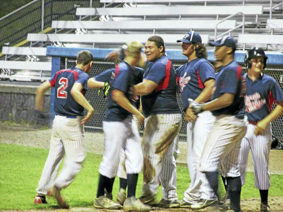 Torrington teammates welcome Riley Shreders home with the winning run. Photo: Photo By Peter Wallace